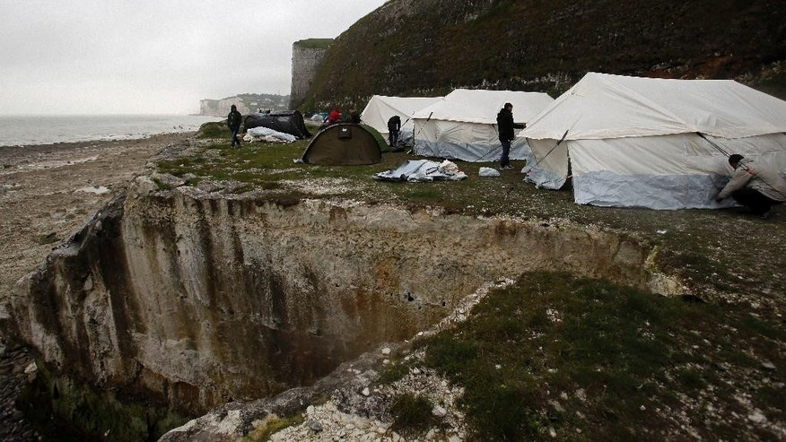 Migrants set up a new makeshift camp along the storm-hit cliffs near the port of Dieppe, northern France, Wednesday, June 1, 2016.  A group of around 150 Albanian migrants are setting up the new camp near the English channel and hoping to be able cross into the UK. (AP Photo/Michel Spingler)