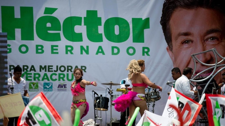 "In this May 18, 2016 photo, women in feathered bikinis dance in front of an electoral banner with an image of Hector Yunes Landa, candidate for Governor for the Institutional Revolutionary Party, PRI, and the coalition ""Para Mejorar Veracruz,"" or ""For Improving Veracruz,"" during a campaign rally in Cosoleacaque, in the gulf coast state of Veracruz, Mexico. The upbeat spectacle is part of efforts to burnish the battered image of the PRI in Veracruz, a state it's never lost despite years of drug cartel violence, looted government coffers and multiple unsolved murders of journalists. (AP Photo/Eduardo Verdugo)"
