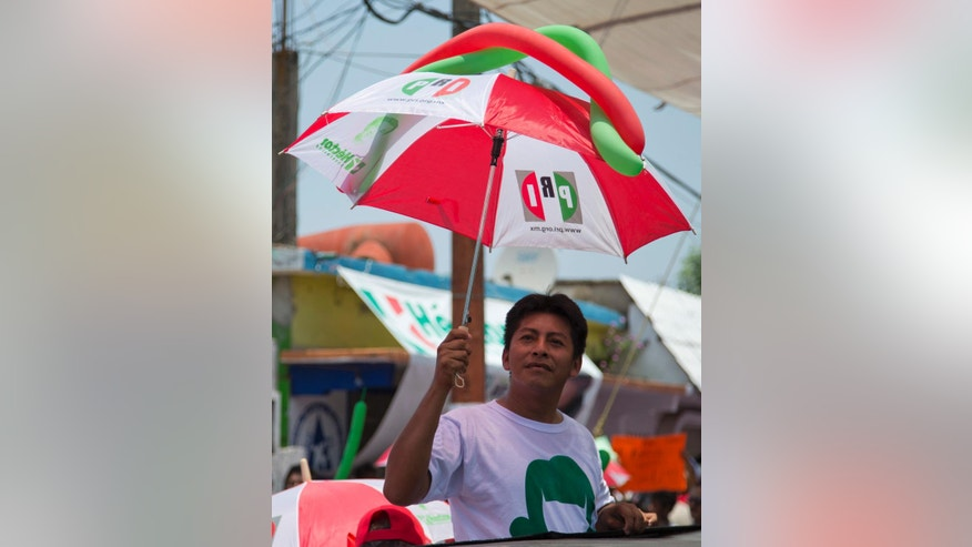 In this May 18, 2016 photo, a supporter protects himself from the sun with a party themed umbrella as he waits for the Institutional Revolutionary Party, PRI, candidate for Governor Hector Yunes Landa, during a campaign rally in Cosoleacaque, in the gulf coast state of Veracruz, Mexico. Polls indicate the PRI has a fighting chance to win yet again in Veracruz and most of the other 11 states holding elections on Sunday, June 5, victories that could smooth its path to keeping the presidency two years from now. (AP Photo/Eduardo Verdugo)