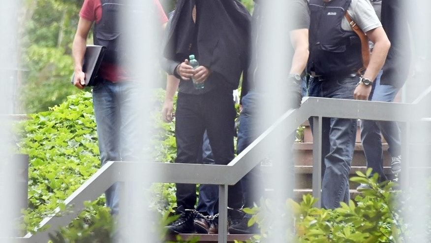 An alleged terror suspect is led by police at the Federal court in Karlsruhe, Germany, Thursday, June 2, 2016. Prosecutors said three Syrian men suspected of planning an attack in Duesseldorf for the Islamic State group have been arrested in Germany. They say a fourth suspect, who informed officials in Paris about the plot, was already in custody in France. (Uli Deck/dpa via AP)