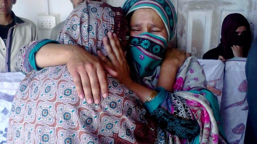 Pakistani family members of a female teacher who was beaten and set on fire, comfort each other in Upper Dewal, Pakistan, Thursday, June 2, 2016. Pakistani police say they have arrested two suspects and are continuing their search for five men who tortured a 19-year-old school teacher and burned her to death for refusing to marry a man twice her age. (AP Photo/Muhammad Yousaf)