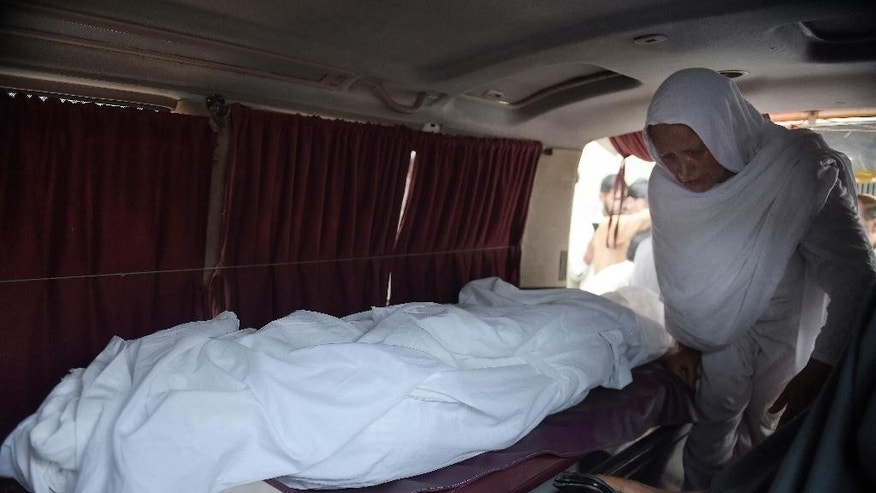 In this picture taken on Wednesday, June 1, 2016, grandmother of a female teacher who was beaten and set on fire, prepares to sit near the body in an ambulance on her way to village, outside a local hospital in Islamabad, Pakistan. Pakistani police say they have arrested two suspects and are continuing their search for five men who tortured a 19-year-old school teacher and burned her to death for refusing to marry a man twice her age. (AP Photo/M. Farid)