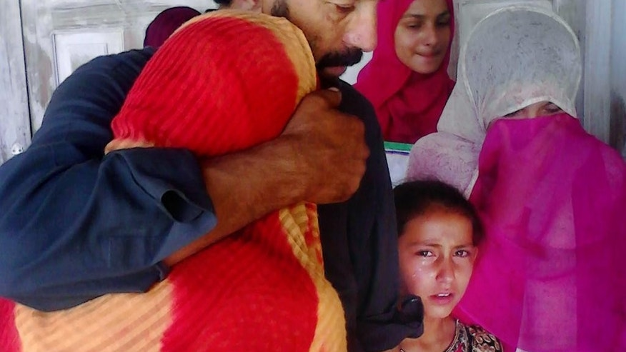 Sadaqat Abbasi, father of a female teacher who was beaten and set on fire, tries to comfort his daughters in Upper Dewal, Pakistan, Thursday, June 2, 2016. Pakistani police say they have arrested two suspects and are continuing their search for five men who tortured a 19-year-old school teacher and burned her to death for refusing to marry a man twice her age. (AP Photo/Muhammad Yousaf)