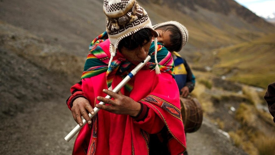 In this May 24, 2016 photo, a pilgrim carrying his son on his back, plays a traditional Andean flute known as a quena, as he walks the five miles to the Sanctuary of the Lord of the Qoyllur Rit'i, to take part in the syncretic festival of the same name, translated from the Quechua language as Snow Star, in the Sinakara Valley, in Peru's Cusco region. (AP Photo/Rodrigo Abd)