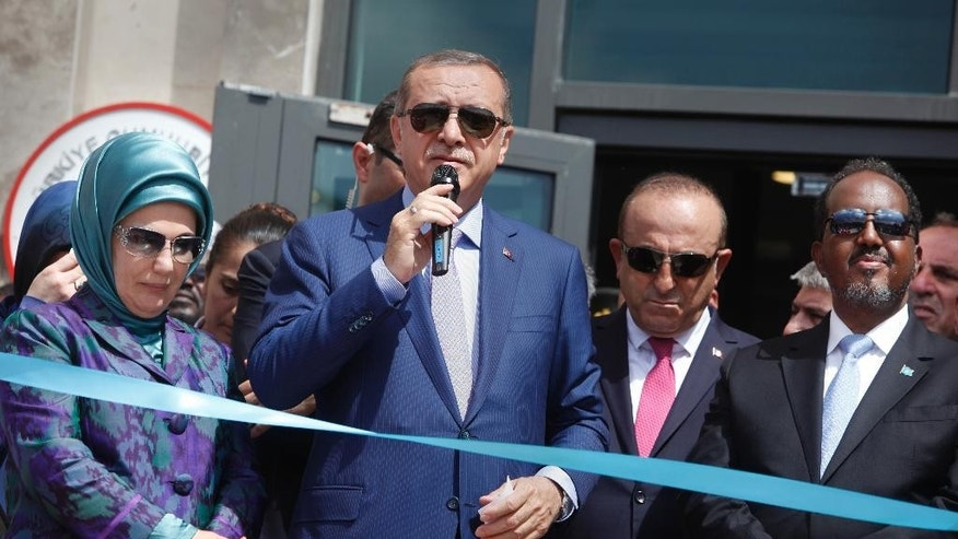 From left to right; Turkey's First Lady Emine Erdogan, Turkey's President, Recep Tayyip Erdogan, Turkey's Foreign Minister, Mevlut Cavusoglu, and Somalia's President, Hassan Sheikh Mohamud, cut the ribbon at a ceremony to open a new Turkish embassy in Mogadishu, Somalia Friday, June 3, 2016. Erdogan opened the new Turkish embassy in Somalia's capital on Friday amid heavy security less than two days after militants attacked a hotel in the city, killing 15 people. (AP Photo/Farah Abdi Warsameh)