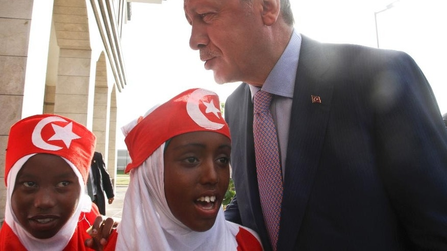 Turkey's President Recep Tayyip Erdogan speaks to Somali girls wearing clothes in the colors of the Turkish flag, outside the new Turkish embassy in Mogadishu, Somalia Friday, June 3, 2016. Erdogan opened the new Turkish embassy in Somalia's capital on Friday amid heavy security less than two days after militants attacked a hotel in the city, killing 15 people. (AP Photo/Farah Abdi Warsameh)