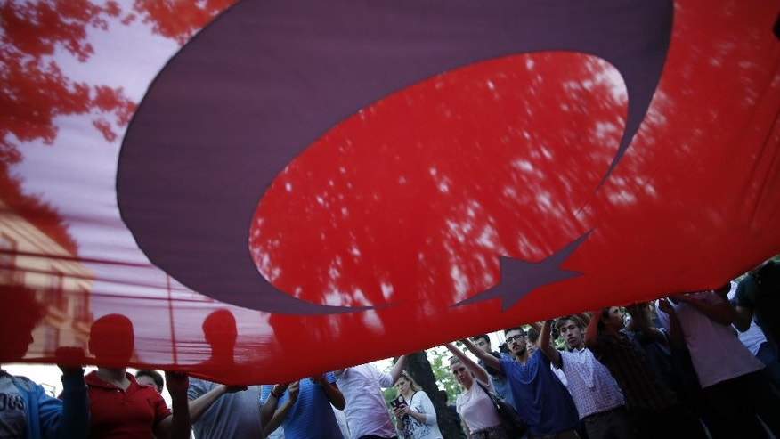 Turkish protesters connected with Turkey's opposition Nationalist Movement Party (MHP), hold a big Turkish flag, during a rally outside the German consulate in Istanbul, Thursday, June 2, 2016. The protesters rallied against the decision made by the German parliament earlier Thursday that overwhelmingly voted to label the killings of Armenians by Ottoman Turks a century ago as genocide, prompting Turkey to recall its ambassador to Germany. (AP Photo/Emrah Gurel)