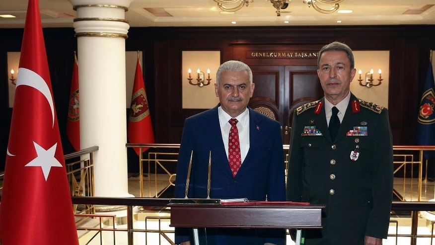 """Turkey's Prime Minister Binali Yildirim, left, stands with Chief of Staff Gen. Hulusi Akar at the headquarters of Turkish army in Ankara, Turkey, Thursday, June 2, 2016. Yildirim says Turkey is recalling its ambassador to Germany for consultations after what he calls a """"historic error"""" by the German parliament to recognize the killings of Armenians by Ottoman Turks a century ago as genocide. (Prime Ministry Press Service/Pool via AP)"""