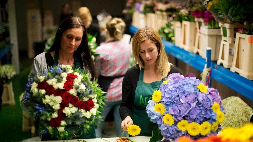 "Arenaflowers.com representatives Asta Foufas, left, and Lizzie Tree pose for photographs while making their ""Stay or Leaf"" EU referendum themed ""Brexit Bouquet"", left, and ""Stronger In Arrangement"" in west London, Thursday, June 2, 2016. British voters will decide in a June 23 referendum whether or not to deal a historic hammer blow to European integration by putting their island nation on an independent path outside the European Union. (AP Photo/Matt Dunham)"