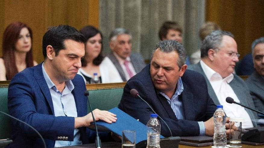 Greek PrIme minister Alexis Tsipras, left, and Greek Defense Minister and party leader of the Independent Greeks Panos Kamenos chat during a cabinet meeting on Thursday, June 2, 2016. Parliament approved a final round of austerity measures Thursday demanded by lenders for the release of further bailout loan installments. (AP Photo/Petros Giannakouris)