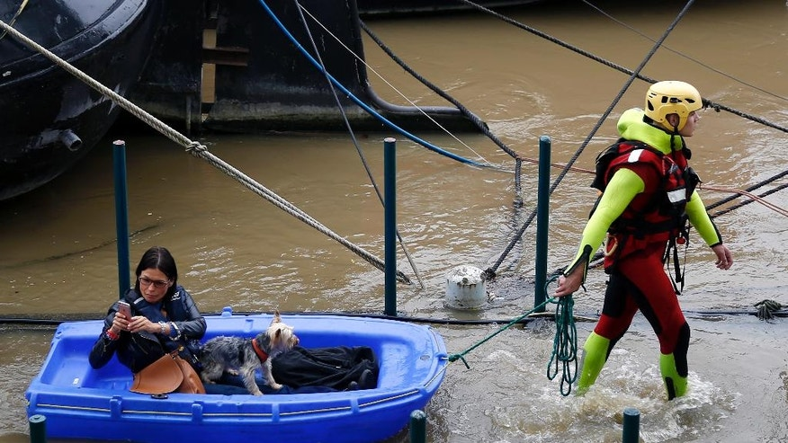 A fireman pulls a woman and her dog to shore, by a row of houseboats on the river Seine in Paris France, Wednesday June 1, 2016. The Seine River has overflowed embankments in Paris as floods hit or threaten cities and towns around France.(AP Photo/Jerome Delay)