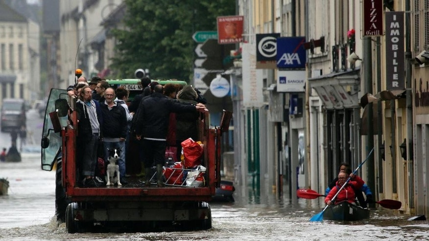 Residents evacuate their home in Nemours, south of Paris, Thursday June 2, 2016. Floods inundating parts of France and Germany have left five people dead and thousands trapped in homes or cars, as rivers have broken their banks from Paris to Bavaria.(AP Photo/Jerome Delay)