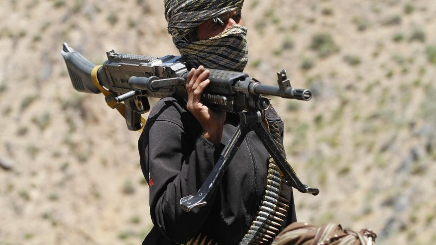 Friday, May 27, 2016: A member of a breakaway faction of the Taliban fighters guards a gathering in Shindand district of Herat province, Afghanistan.