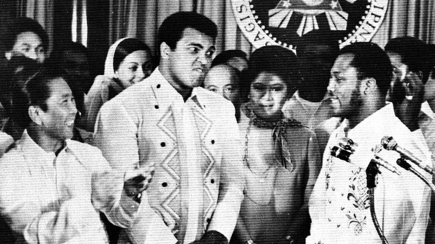 FILE - In this Sept. 18, 1975, file photo, Philippines President Ferdinand Marcos, left, applauds as challenger Joe Frazier, right, makes some remarks about world champion Muhammad Ali, second from left, during their call on Marcos at the Malacanang Palace in Manila, Philippines.  Ali, the magnificent heavyweight champion whose fast fists and irrepressible personality transcended sports and captivated the world, has died according to a statement released by his family Friday, June 3, 2016. He was 74. (AP Photo/Jess Tan, File)