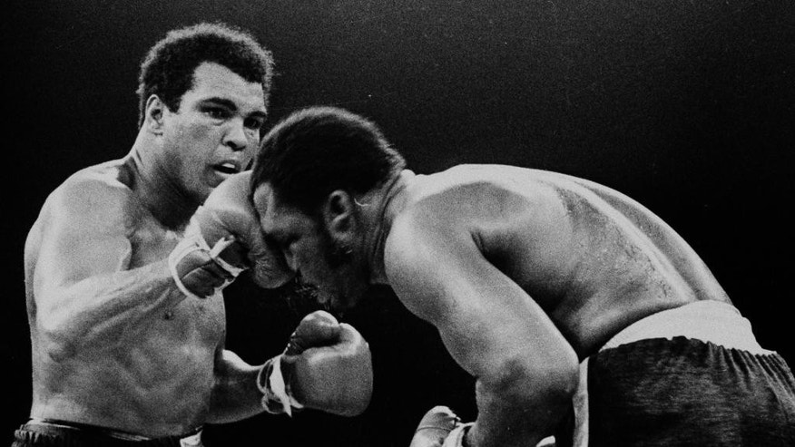 FILE - In this Oct. 1, 1975, file photo, Muhammad Ali's throws a right at Joe Frazier in the 13th round in their title bout in Manila, Philippines. Ali, the magnificent heavyweight champion whose fast fists and irrepressible personality transcended sports and captivated the world, has died according to a statement released by his family Friday, June 3, 2016. He was 74. (AP Photo/FILE)