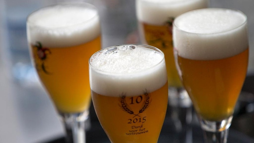 Glasses of Brugse Zot beer stand on a serving tray at the Halve Maan Brewery in Bruges, Belgium on Thursday, May 26, 2016. The brewery has recently created a beer pipeline which will ship beer straight from the brewery to the bottling plant, two kilometers away, through underground pipes running between the two sources. (AP Photo/Virginia Mayo)