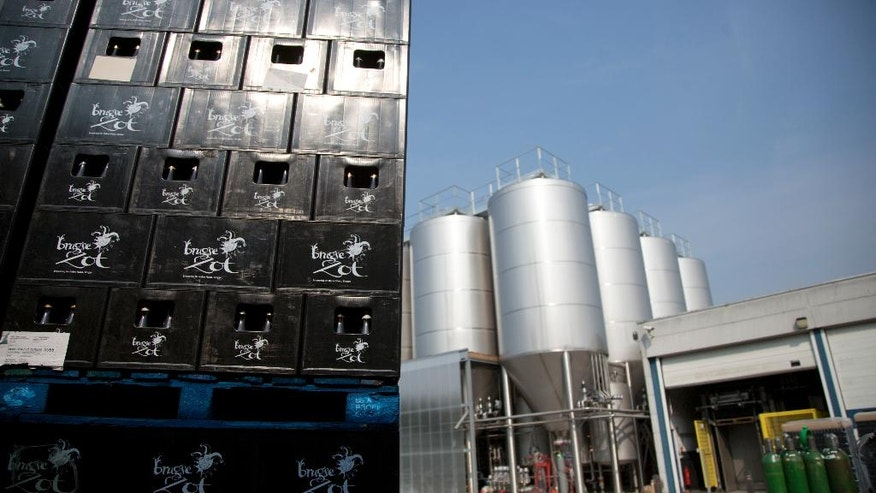 Cases of beer and vats full of beer at the Halve Maan bottling plant on the outskirts of Bruges, Belgium on Thursday, May 26, 2016. The brewery has recently created a beer pipeline which will ship beer straight from the brewery to the bottling plant, two kilometers away, through underground pipes running between the two sources. (AP Photo/Virginia Mayo)