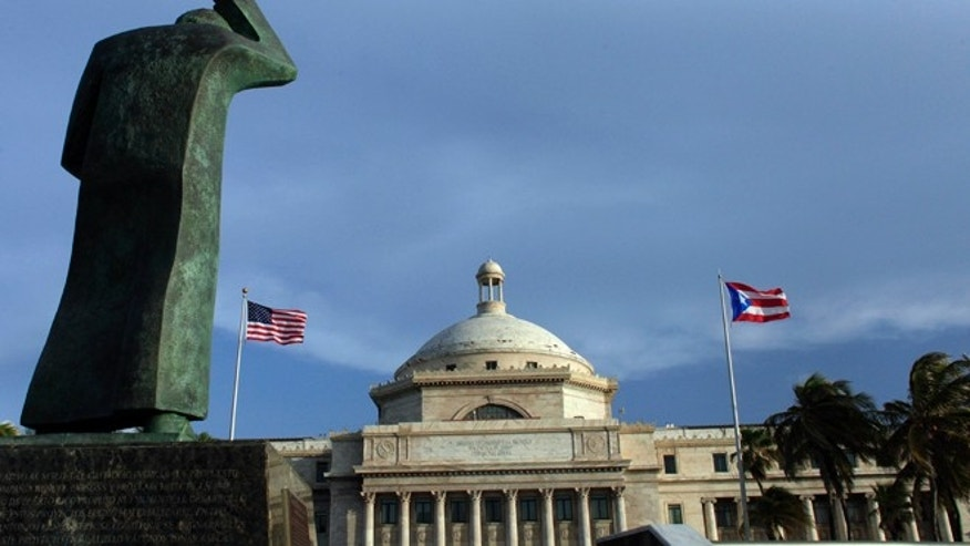 FILE - In this Wednesday, July 29, 2015, file photo, a bronze statue of San Juan Bautista stands in front of Puerto Ricoâs Capitol as U.S. and Puerto Rican flags fly in San Juan, Puerto Rico. After months of pleading from the government of Puerto Rico, the U.S. Congress agreed on Wednesday, May 18, 2016, to help the territory restructure its massive public debt. (AP Photo/Ricardo Arduengo, File)