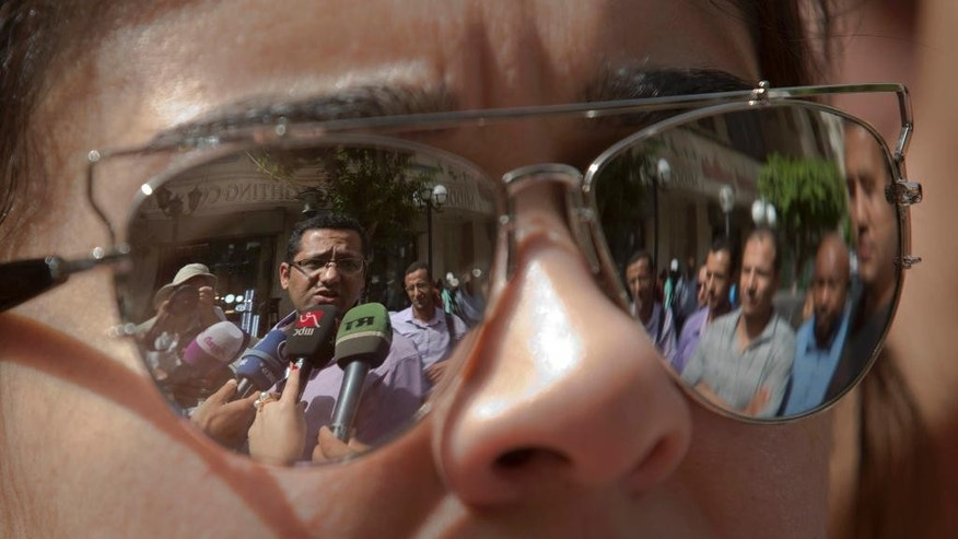 Khaled El-Balshy, Head of Journalists Syndicate's Freedoms Committee, is reflected in a reporter's sunglasses as he arrives at Cairo south court in Cairo, Egypt, Saturday, June 4, 2016. The head of Egypt's journalists union and two of its board members are on trail over allegations that they harbored journalists wanted by authorities and spread false news. (AP Photo/Amr Nabil)