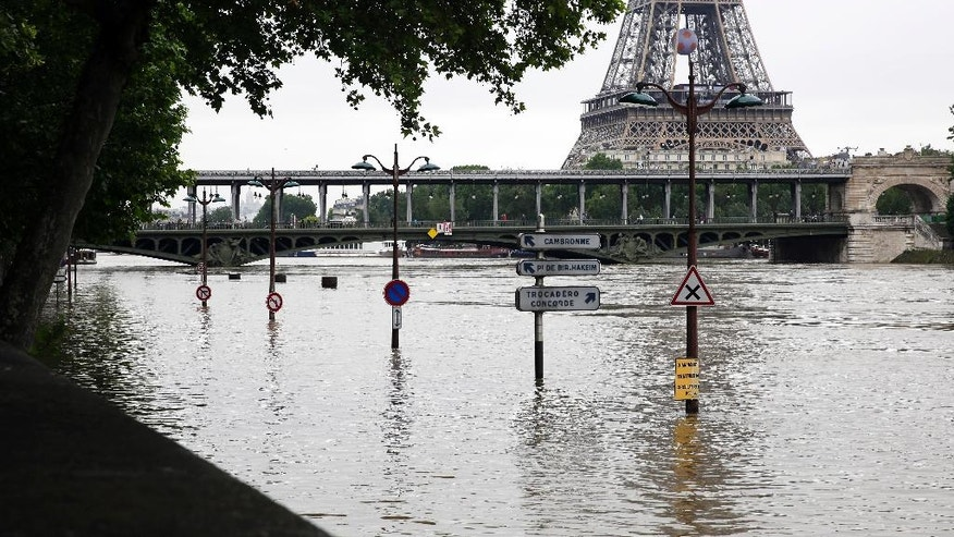 View of the flooded banks of the river Seine in front of the Eiffel tower in Paris, Friday, June 3, 2016. Both the Louvre and Orsay museums were closed as the Seine, which officials said was at its highest level in nearly 35 years, was expected to peak sometime later Friday.(AP Photo/Jerome Delay)