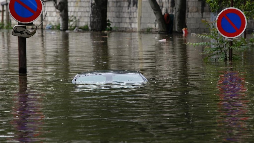 The roof of a car parked in a marked no parking zone sticks out of the water on the flooded banks of the Seine river near the Eiffel tower in Paris, Friday June 3, 2016. Both the Louvre and Orsay museums were closed as the Seine, which officials said was at its highest level in nearly 35 years, was expected to peak Friday. (AP Photo/Jerome Delay)