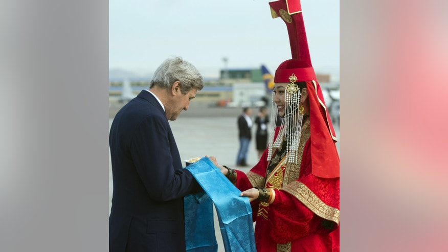 US Secretary of State John Kerry samples cheese curds alongside a woman in traditional attire as he disembarks from his airplane upon arrival at Chinggis Khaan International Airport in Ulaanbaatar, Mongolia, June 5, 2016. (Saul Loeb/Pool Photo via AP)