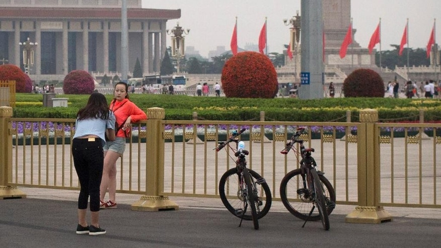 A girl poses for a photo along the barriers surrounding Tiananmen Square in Beijing, Saturday, June 4, 2016. Saturday marks the 27th anniversary of China's bloody crackdown on pro-democracy protests centered on Beijing's Tiananmen Square. (AP Photo/Mark Schiefelbein)