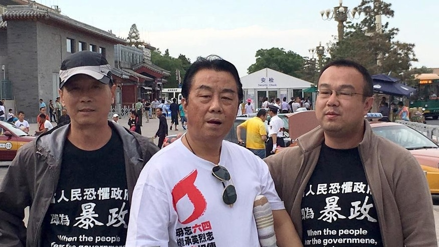"In this May 29, 2016 photo, Qi Zhiyong, cetner, who lost a leg when he was shot by Chinese troops as they crushed pro-democracy demonstrations around Tiananmen Square on June 3 and 4, 1989, and June 4 commemoration supporters Jiang Jianjun, left, and Wang Fulei, right, pose for a photo near Tiananmen Square in Beijing. Security was tightened around Tiananmen Square on the 27th anniversary Saturday, June 4, 2016 of China's bloody military crackdown on student-led pro-democracy protests, pointing to the enduring sensitivity over the events with the Chinese leadership. At least half a dozen people have reportedly been detained in recent days for attempting to commemorate the events, although a small group, including Qi, wearing T-shirts condemning the crackdown converged on the square last Sunday. Qi's T-shirt reads: ""Always remember June 4, inherit the ambition of the martyrs, pass on the torch, hold the baton of democracy."" (Photo via AP) NO SALES, NO ARCHIVE"