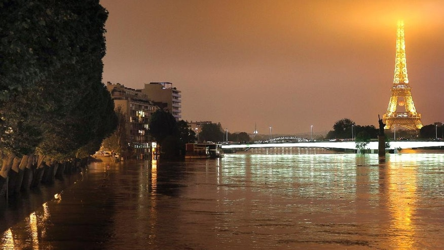 View of the flooded banks of the river Seine in front of the Eiffel tower in Paris, Friday, June 3, 2016. Both the Louvre and Orsay museums were closed as the Seine, which officials said was at its highest level in nearly 35 years, was expected to peak sometime later Friday. (AP Photo/Christophe Ena)