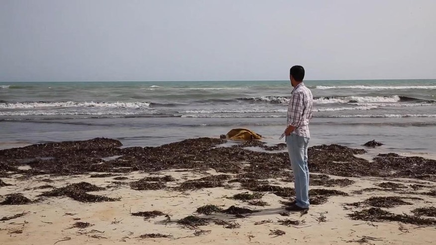 A local Zwara resident views the body of a victim, laying in the surf at centre, as more than 100 bodies are pulled from the sea near the western city of Zwara, Libya, Friday June 3, 2016, after a smuggling boat carrying mainly African migrants sank into the Mediterranean.  Libya's navy spokesman Col. Ayoub Gassim says that the bodies of more than 100 migrants have been retrieved, but the death toll is likely to be higher. (APTV via AP) TV OUT