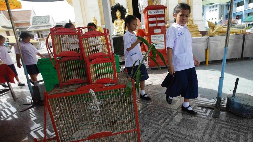 In this photo taken on June 3, 2016, Thai students walk past caged birds sold to be released for good luck at the Wat Trimitr temple in Bangkok, Thailand. The scandal surrounding Thailand's Tiger Temple, where wildlife officers seized 137 big cats this past week, has cast religious sanctuaries for animals in a bad light. The shady findings of the raids aside, Buddhism and animals have an intrinsic link loosely derived from Buddhist precepts promoting compassion for living beings. (AP Photo/Sakchai Lalit)