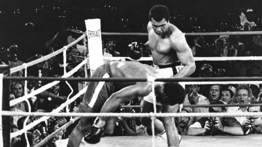 FILE - This is a Oct. 30, 1974  file photo   Muhammad Ali  watches George Foreman head for the canvas after being knocked out in the eighth round of their match in Kinshasa, Zaire.  Ali, the magnificent heavyweight champion whose fast fists and irrepressible personality transcended sports and captivated the world, has died according to a statement released by his family Friday, June 3, 2016. He was 74. (AP Photo, File)