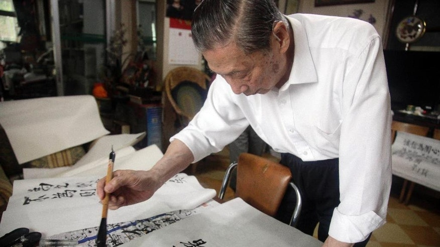 In this May 25, 2016 photo, Mao Yushi writes calligraphy at home in Beijing. Targeted by radical Red Guards during China's tumultuous Cultural Revolution, Mao Yushi saw his family home ransacked, underwent hard labor and was lashed bloody with copper wires along with his father. Fifty years later, Mao's campaign to document China's turbulent past and hold the ruling Communist Party accountable continues to win him enemies among die-hard acolytes of Mao Zedong, who unleashed the Cultural Revolution in 1966 a bid to revive his radical egalitarian agenda. (AP Photo/Gerry Shih)