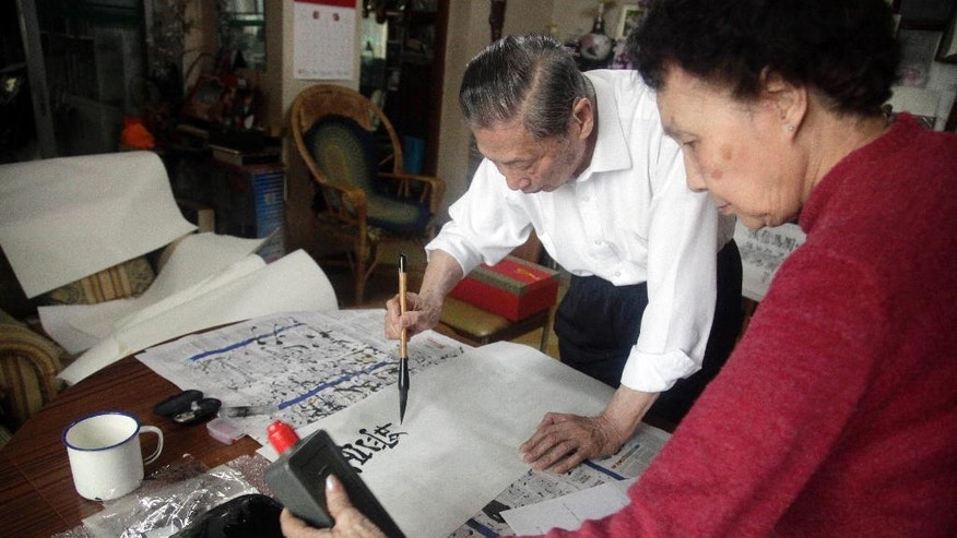 In this May 25, 2016 photo, Mao Yushi writes calligraphy as his wife Zhao Yanling prepares the ink at their home in Beijing. Targeted by radical Red Guards during China's tumultuous Cultural Revolution, Mao Yushi saw his family home ransacked, underwent hard labor and was lashed bloody with copper wires along with his father. Fifty years later, Mao's campaign to document China's turbulent past and hold the ruling Communist Party accountable continues to win him enemies among die-hard acolytes of Mao Zedong, who unleashed the Cultural Revolution in 1966 a bid to revive his radical egalitarian agenda. (AP Photo/Gerry Shih)