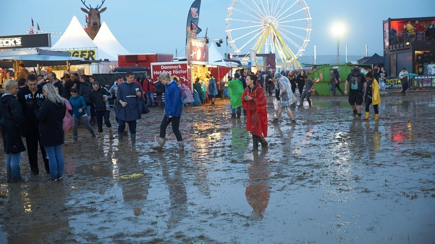 In this Friday June 3, 2016 picture people walk through the mud after a thunderstorm hit the open air music festival ' Rock am Ring' in Mendig, Germany.