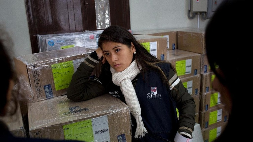An electoral worker rests while listening to her colleagues as voting boxes arrive to a polling station in Lima, Peru, Saturday, June 4, 2016. The South American country is gearing up for a tight June 5th runoff between Keiko Fujimori, the daughter of jailed former President Alberto Fujimori, and former World Bank economist Pedro Kuczynski. (AP Photo/Rodrigo Abd)