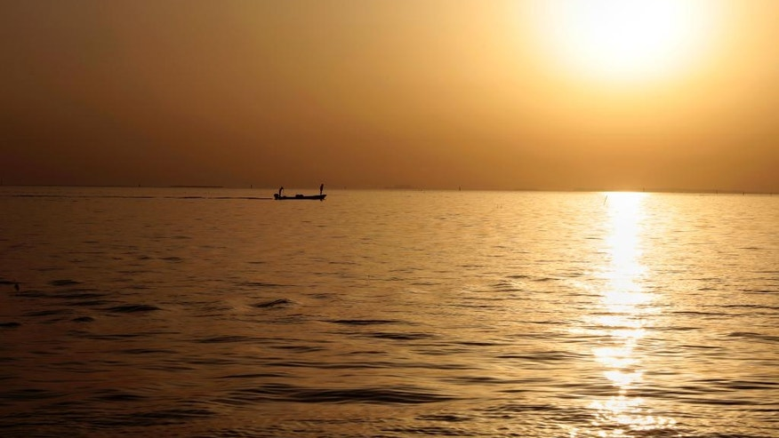 A fishing boat moves through the Persian Gulf at sunset off the coast of Karzakan, Bahrain, Sunday, June 5, 2016. Bahrain announced that Monday would be the first day of the Islamic month of Ramadan, a time Muslims worldwide focus on prayer, fasting and charitable giving. (AP Photo/Hasan Jamali)