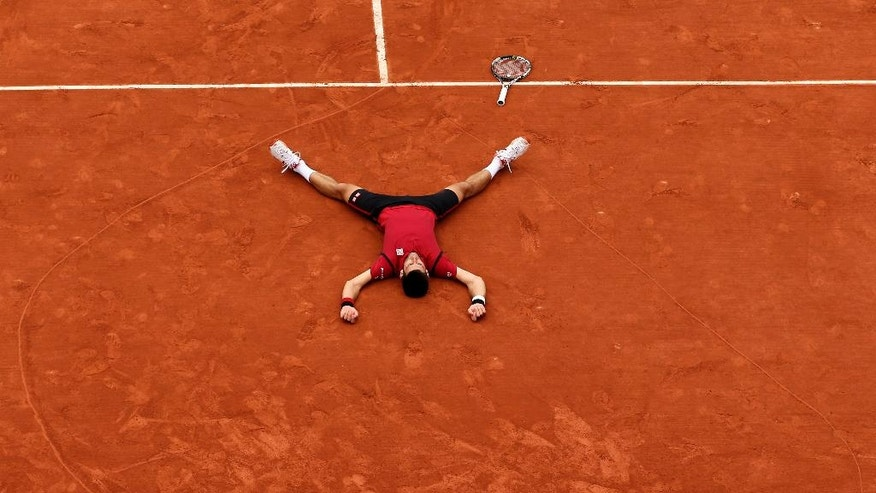 Serbia's Novak Djokovic lays on the clay in a heart  in drew after defeating Britain's Andy Murray during their final match of the French Open tennis tournament at the Roland Garros stadium, Sunday, June 5, 2016 in Paris. Djokovic won 3-6, 6-1, 6-2, 6-4. (AP Photo/David Vincent)