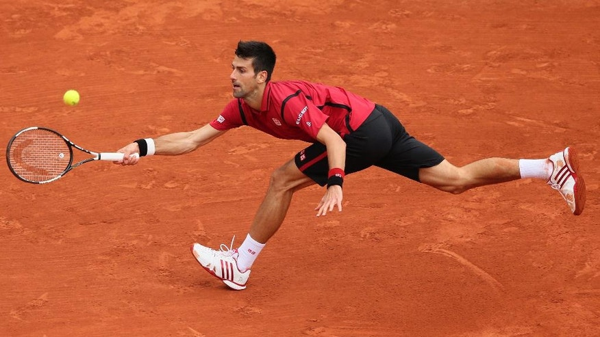 Serbia's Novak Djokovic stretches to return the ball to Britain's Andy Murray during their final match of the French Open tennis tournament at the Roland Garros stadium, Sunday, June 5, 2016 in Paris. (AP Photo/David Vincent)