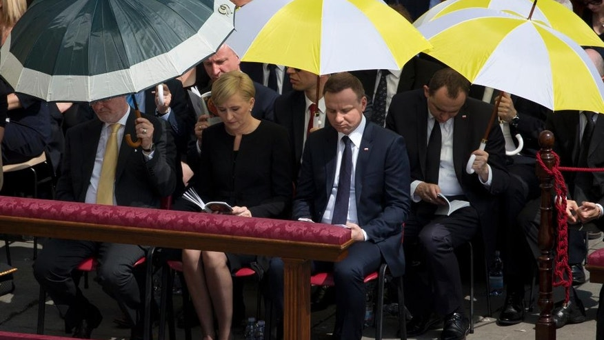 Polish president Andrzej Duda, center and his wife Agata Kornhauser-Duda sit in St. Peter's Square at the Vatican during a canonization ceremony led by Pope Francis, Sunday, June 5, 2016. Pope Francis has canonized Elizabeth Hesselblad, a Lutheran convert who hid Jews during World War II and Stanislaus of Jesus and Mary Papczynski, the founder of the first men's religious order dedicated to the immaculate conception. (AP Photo/Alessandra Tarantino)