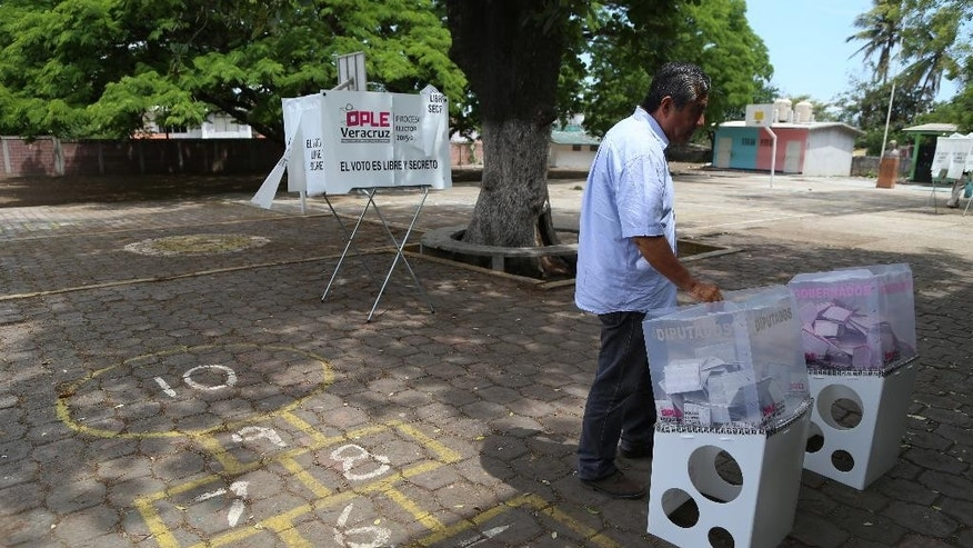 A man casts his vote during state elections in the city of Veracruz, Mexico, Sunday, June 5, 2016. Veracruz is the biggest prize in Sunday's gubernatorial elections, which could shape the fortunes of the country's ruling Institutional Revolutionary Party in its bid to hold onto the presidency in 2018. In five of the 12 statehouses up for grabs, including Veracruz, the party has ruled uninterrupted for more than 80 years. (AP Photo/Ilse Huesca)