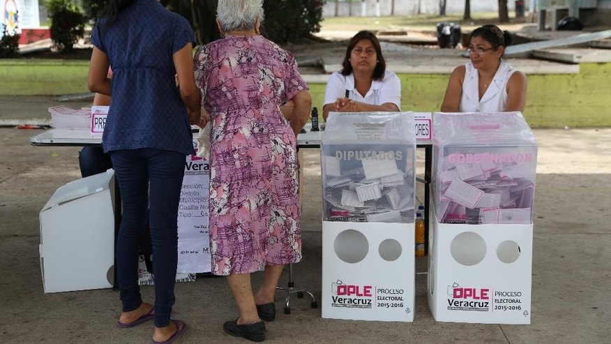 People prepare to cast their vote during state elections in the city of Veracruz, Mexico, Sunday, June 5, 2016. Veracruz is the biggest prize in Sunday's gubernatorial elections, which could shape the fortunes of the country's ruling Institutional Revolutionary Party in its bid to hold onto the presidency in 2018. In five of the 12 statehouses up for grabs, including Veracruz, the party has ruled uninterrupted for more than 80 years. (AP Photo/Ilse Huesca)
