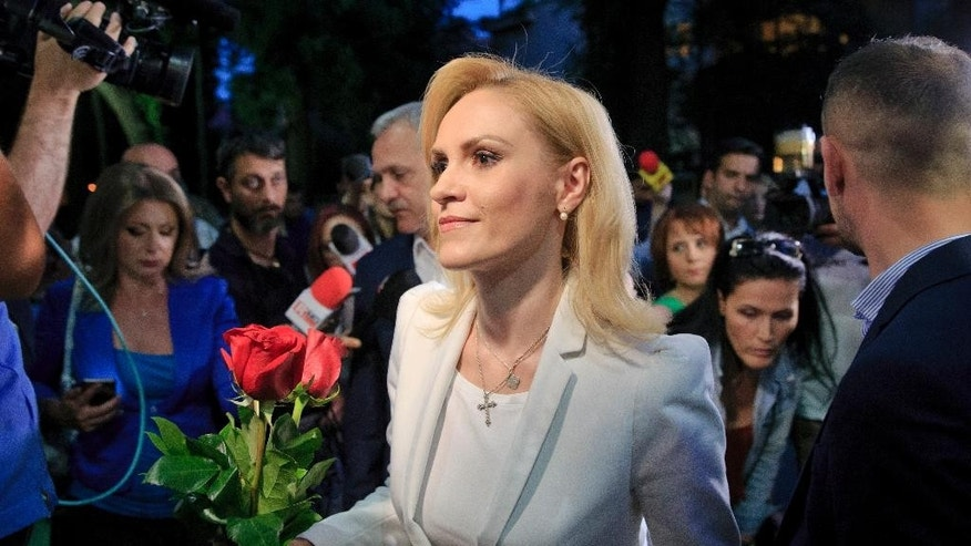 Gabriele Firea holds roses after the press statement that followed the release of exit polls in the local elections indicating she's the new mayor of the Romanian capital in Bucharest, Romania, Sunday, June 5, 2016. Three exit polls showed that Firea, a former TV journalist and member of the center-left Social Democratic Party easily won the post of Bucharest mayor scoring about 41 percent of the vote. (AP Photo/Vadim Ghirda)