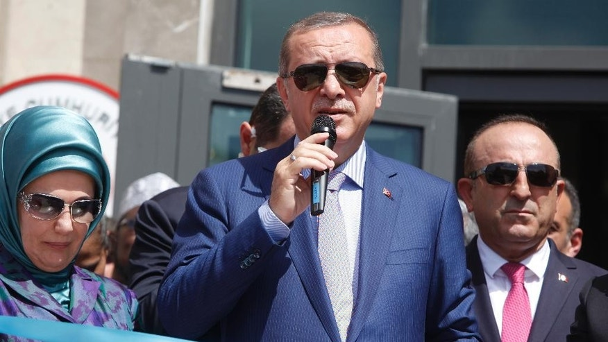 From left to right; Turkey's First Lady Emine Erdogan, Turkey's President Recep Tayyip Erdogan, and Turkey's Foreign Minister Mevlut Cavusoglu attend a ceremony to open a new Turkish embassy in Mogadishu, Somalia Friday, June 3, 2016. Erdogan opened the new Turkish embassy in Somalia's capital on Friday amid heavy security less than two days after militants attacked a hotel in the city, killing 15 people. (AP Photo/Farah Abdi Warsameh)