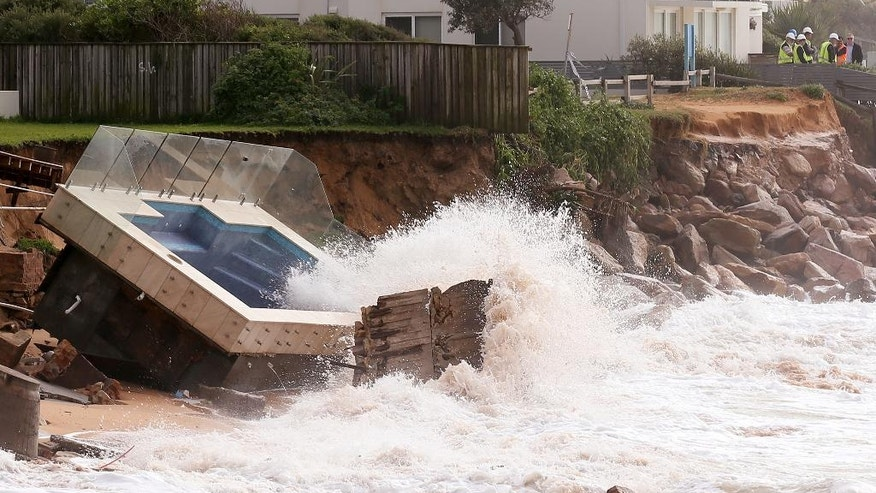 A swimming pool is dislodged and lays on a beach after storms undermined the pilings at Collaroy Beach in Sydney, Monday, June 6, 2016. Storms have lashed Australia's easter coast for several days. (AP Photo/Rick Rycroft)