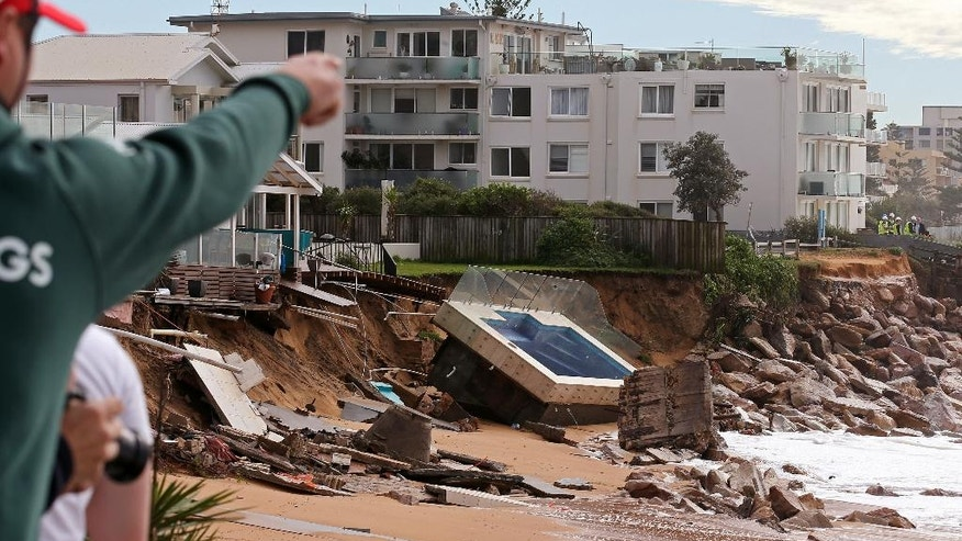A swimming pool is dislodged and lays on a beach after storms undermined the pilings at Collaroy in Sydney, Monday, June 6, 2016. Storms have lashed Australia's easter coast for several days. (AP Photo/Rick Rycroft)