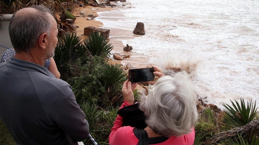 A couple photograph the coastline where a swimming pool has been dislodged and lays on a beach after storms undermined the pilings at Collaroy Beach in Sydney, Monday, June 6, 2016. Storms have lashed Australia's easter coast for several days. (AP Photo/Rick Rycroft)