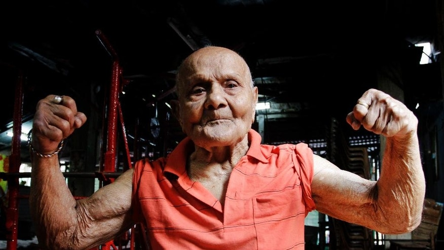 FILE- In this March 16, 2012 file photo, Indian bodybuilder Manohar Aich flexes his muscles as he poses for a photograph at a gymnasium in Kolkata, India. Aich, a celebrated Indian bodybuilder and former Mr. Universe, has died in the eastern city of Kolkata at the age of 104. Aich's son said his father died Sunday, June 5, 2016 from health issues related to his age. (AP Photo/Bikas Das, File)