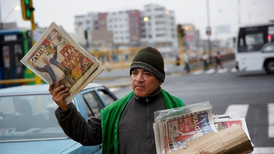 "A newspaper vendor holds up a tabloid with a headline that reads in Spanish; ""PPK to the Palace"", referring to presidential candidate Pedro Pablo Kuczynski,  in Lima, Peru, Monday, June 6, 2016. Early exit polls show Kuczynski with a slight lead over his rival Keiko Fujimori in Peru's runoff presidential election. (AP Photo/Rodrigo Abd)"