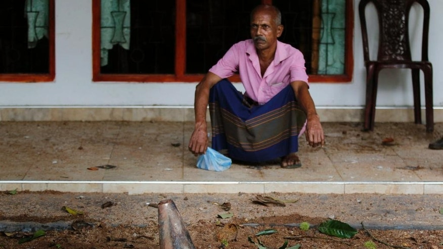 A Sri Lankan man sitting in front of his damaged house where an unexploded artillery shell is seen fallen following a fire at a military base in Salawa, about 35 kilometres (22 miles) east of Colombo, Sri Lanka, Monday, June 6, 2016. Minister of Law and Order Sagala Ratnayake said the fire started at a small arms depot and then spread to other depots where heavy weapons, such as artillery shells, were stored. (AP Photo/Eranga Jayawardena)